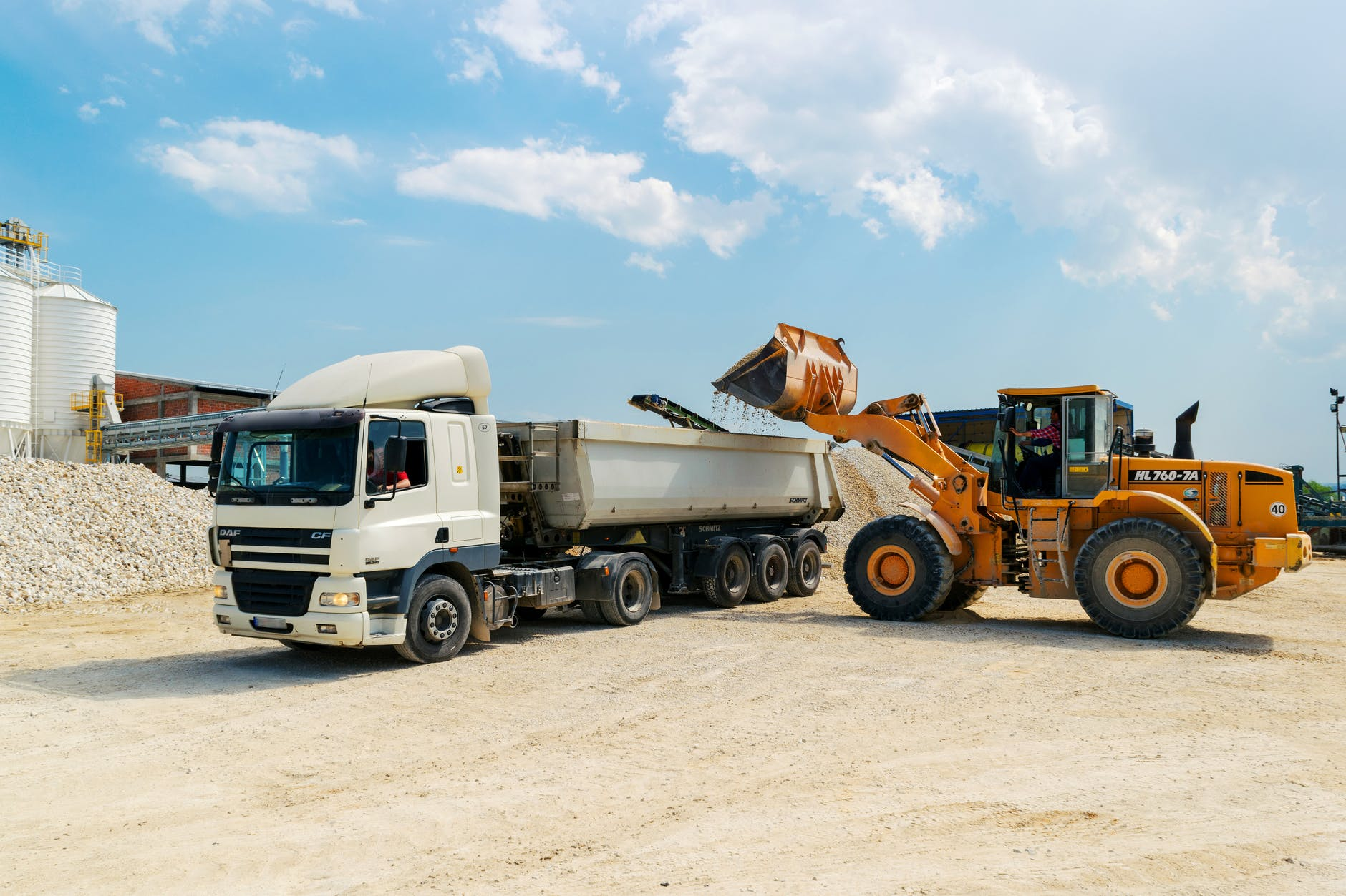 brown loader beside white cargo truck