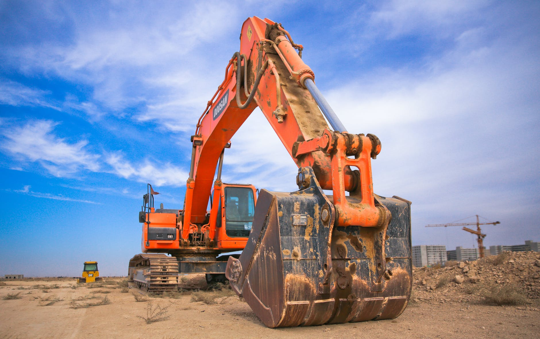 low angle photography of orange excavator under white clouds