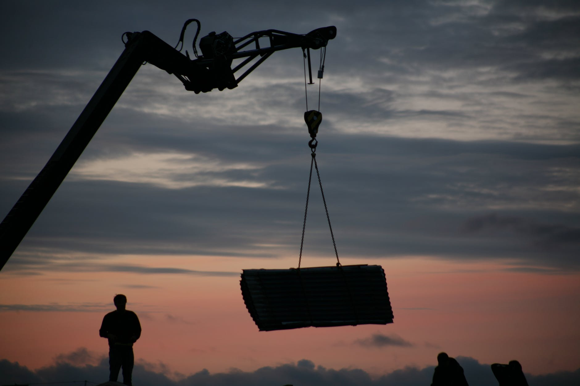 crane lifting concrete layer near silhouettes of workmen at sunset